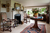 Antique armchairs and round table in front of fireplace in interior of renovated English country house
