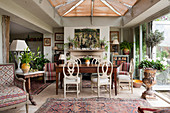 Dining table and antique chairs in front of fireplace in renovated English country house