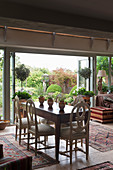 Dining table and antique chairs in front of open terrace doors in English country house