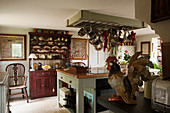 English country-house kitchen with antique dresser and rack suspended over island counter