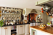 Dresser, AGA cooker and island counter in English country-house kitchen