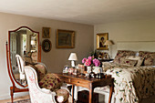 Antique cheval mirror, dressing table with armchair and bed with floral quilt in bedroom