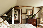 Bedroom with low ceiling and half-timbered wall in English country house