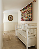 Ethnic wall hanging above white wooden bench in hall