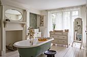 Free-standing bathtub in classic, white bathroom