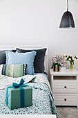Gift on bed with bedspread and pillow in shades of blue