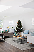Bright living room decorated for Christmas with sofa and coffee table