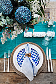 Laid table in aqua tones with floral decoration and table runner