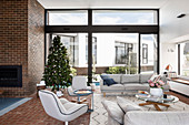 Gray upholstered furniture in the living room with window front and Christmas tree