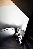 Boy on dark and modern spiral staircase