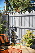 Outdoor shower on the fence in the sunny garden with terrace