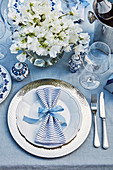 Festive table setting with silver place plate, blue-striped napkin and bouquet