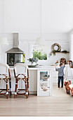 Children and dog in bright white kitchen with bar stools on kitchen island