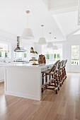 Bright white kitchen with bar chairs lined up on a spacious kitchen island