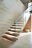 Wooden stairs with glass railings in an ecological architect's house