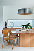 Designer lamp over dining table with wooden chairs next to window hinge