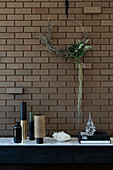 Minimalist wreath on the brick wall above the sideboard