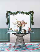 Round metal and glass table with bouquet and gifts in front of passage with Christmas garland