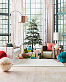 Wrapped gifts under Christmas tree, sofa and armchair in living room with glass walls