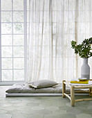 Floor mat with pillows in front of a window next to a side table with a vase