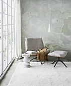 Chair with linen upholstery and footrest in sitting area by the window