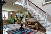 Antique furniture and white staircase in spacious foyer