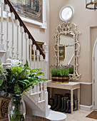 Ornate mirror above console table at foot of staircase in foyer