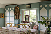 Blue-and-white bedroom with fitted wardrobes and brass bed