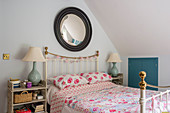 Fisheye mirror above metal bed with rose-patterned quilt
