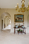 Sandstone flags and chandelier in foyer and arched passageway in English manor house