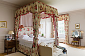 Four-poster bed with chintz curtains in bedroom in English manor house