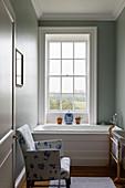 White-and-blue armchair next to bathtub below lattice window
