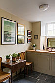 Vintage poster above antique drop-leaf table in bathroom