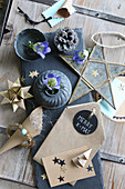 Handcrafted Christmas decorations made from brown paper and gentian in small pewter dish and vase