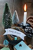 Kleine Tannenbäumchen, brennende Kerze und Xmas-Schild