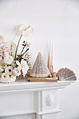 White floral arrangement, paper decoration and candles on mantelpiece