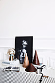 Cone-shaped decorative objects, books, table lamp and black and white photography on a sideboard