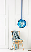 Blue paper star against white wall and chair with blanket