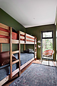 Two bunk beds in a narrow room with green walls