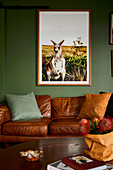 Picture of a kangaroo on a green wall above a brown leather sofa in the living room