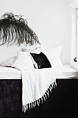 Day bed with pillows and fringed blanket