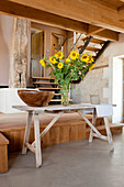 Wooden bowl and vase of sunflowers on table in converted barn