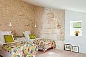 Zwei Betten in ländlich rustikalem Schlafraum mit Natursteinwänden