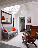 Old rocking chair and modern grey sofa in attic room