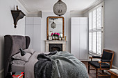 Open fireplace in classic bedroom in shades of grey