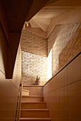 Stairwell with wood panelling and brick walls