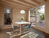 Runder Tisch mit Klassikerstühlen vor Glasschiebetür