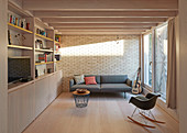 Sofa and shelves in modern living room with brick wall and balcony door