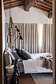 Bedroom in shades of grey with wooden ceiling beams