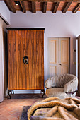 Wardrobe with wood-veneer front next to modern armchair